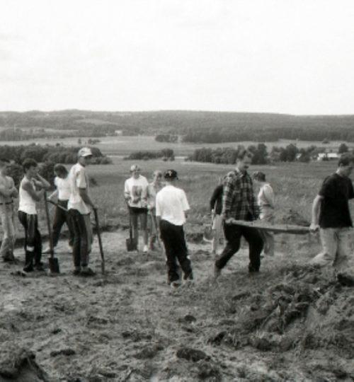1996 m. Kernavės-Kriveikiškio kapinyno tyrinėjimai. Velėnos nuėmimas. Tradiciškai pirmą neštuvą neša tyrimų vadovai G. Vėlius (pirmas) ir A. Luchtanas